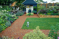 Blue shed gazebo at back of lovely yard with brick paths, central lawn grass feature,  & raised perennial beds, privacy fence, lavender herb in bloom in drifts, driftwood