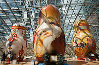 Moscow, Russia, 15/06/2011..A woman walks through an exhibition of of giant Russian matryoshki, or nesting dolls, in the newly-opened Afimall shopping centre. The dolls, designed by Boris Krasnov, are from 6 to 13 metres high, and each is decorated in a different style of traditional Russian folk art..Left - right: Russian Imperial porcelain, Fedoskono, and Gorodetskaya styles..