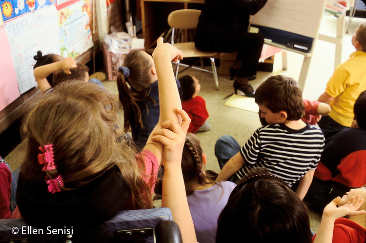 MR / Schenectady, NY.Zoller Public School - Inclusion Class - Grade 1.Girl (6, Afghani-Am) helps girl (6, cerebral palsy) hold her hand up ( a difficult task for her)..MR: Zah1, Her4.PN#: 28649                      FC#: 21603-00510.scan from slide.© Ellen B. Senisi