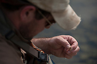 150620-JRE-7981E-0024 Cal Trout, a teacher and quail hunting guide from Mississippi, ties on a fly while fishing for Arctic Grayling.