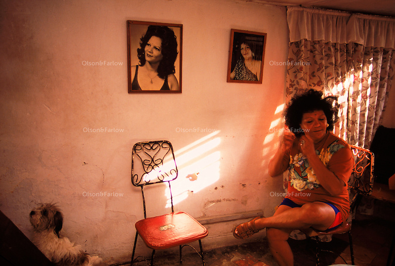 Ana Maria Chomat has worked as a singer for many years throughout Havana. Pictures of her in earlier years grace her bedroom wall. She prepares to sing at a party in the evening. Her son followed her in music and plays with Santana on the album Supernatura.