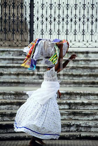 Salvador, Bahia, Brazil. Bahiana woman carrying a basket of scarves on her head outside the church of Nosso Senhor do Bonfim.