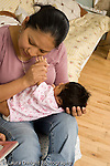 newborn baby girl one month old  Mexican American held by mother inteaction vertical