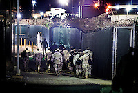 Night guards from Camp Delta walk to their posts to take over the nightshift at the American naval base at Guantanamo Bay, where over 600 alleged al Qaeda members have been held indefinitely. Described by the US as 'unlawful enemy combatants', they were captured primarily in Afghanistan during the 'war against terror'.