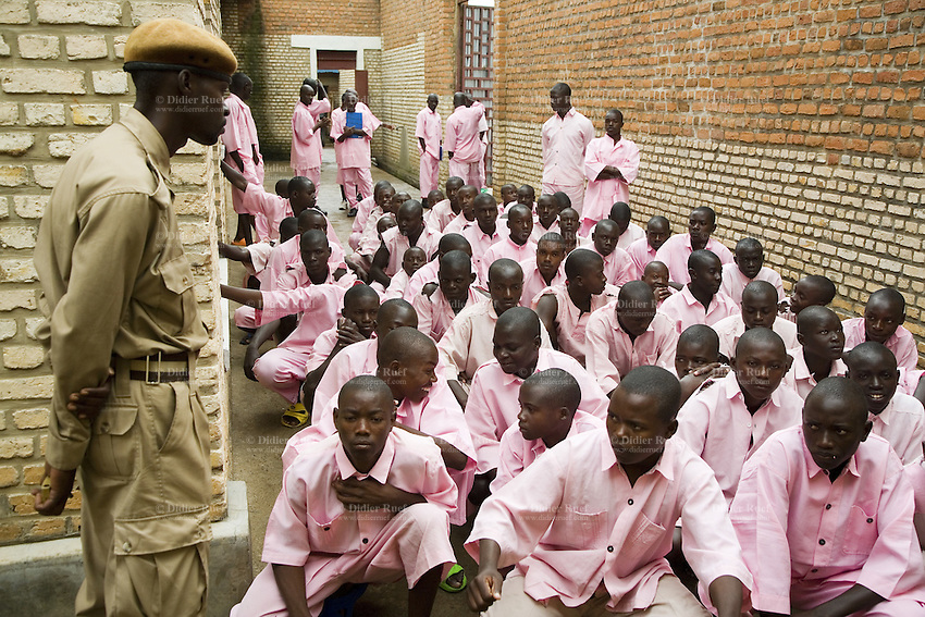 Rwanda. Southern province. District of Muhanga. Central jail of Gitarama. A group of black teenager boys, wearing the pink prisoner's clothes, kneel down. A prison warder, dressed with a beige sandy army uniform, stands up. A group of black men, all working as teachers and pending trial for the 1994 genocide, are standing up in the back of the alley. Bricks wall. Minors block. Minors in detention. Detention pending trial and after trial, when sentenced to prison. The non-governmental organization (NGO) Fondation DiDé - Dignité en détention runs the Encademi (Encadrement des mineurs) program. Prison centrale de Gitarama. Quartier des mineurs.  © 2007 Didier Ruef