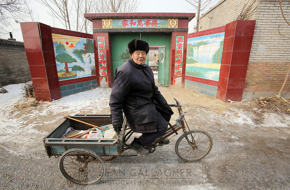 A villager in Dongzhuangying village in front of an elaborate and newly built gate, on the southern outskirts of Beijing. Villagers have been building new extensions to their properties in-light of news that their village will be destroyed to make way for a new city airport. Villagers will be compensated more depending on the area of their homes, resulting in new buildings appearing across the village, as villagers anticipate higher amounts of compensation from local government. China. Friday 25th January, 2013.