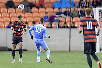 Houston, TX - Friday December 9, 2016: Brian Nana-Sinkam (8) of the Stanford Cardinal heads the ball away from his goal against the North Carolina Tar Heels at the NCAA Men's Soccer Semifinals at BBVA Compass Stadium in Houston Texas.