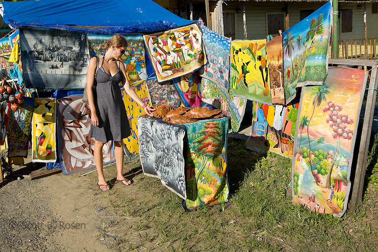 Female tourist looks at local artisenia and paintings on Calle 3, Bocas Town, Bocas del Toro, Panama
