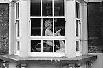 Woman in her curlers putting up lace curtains.  Whitechapel London England. 1975