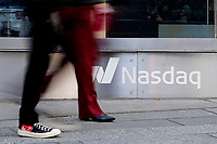 NEW YORK, NEW YORK - MARCH 10: People walk in front Nasdaq at Times Square on March 10, 2021, in New York. The Nasdaq Composite continued falling more than half a percent during the day also the move away from Apple Inc, Amazon.com Inc , Facebook Inc, Tesla Inc and Microsoft Corp, falling during the day, helped small-cap stocks rise more than double the gains of the S&P 500. (Photo by John Smith/VIEWpress)