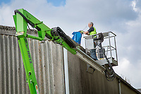 Using a cherry picker and safety harness to safely clean farm building gutters