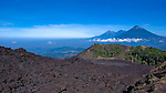 View of the volcanic peaks of Agua, Fuego, and Acatenango from the lava of Volcan de Pacaya, Guatemala