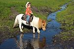 Colten White riding his miniature horse across the creek at the Guidetti Ranch Roundup, San Luis Obispo, California