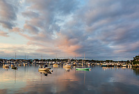 The rising sun adds color to dramatic clouds over sunlit sailboats and other pleasure craft moored in the harbor shortly after sunrise in Oak Bluffs, Massachusetts on Martha's Vineyard.