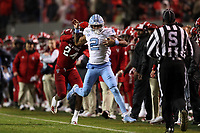 RALEIGH, NC - NOVEMBER 30: Dyami Brown #2 of the University of North Carolina is knocked out of bounds by Malik Dunlap #24 of North Carolina State University during a game between North Carolina and North Carolina State at Carter-Finley Stadium on November 30, 2019 in Raleigh, North Carolina.