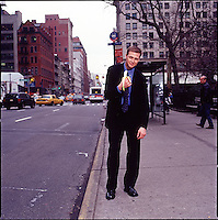 Man in suit standing on sidewalk holding a banana and posturing as an ape<br />
