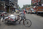 Daily wage laborers carry goods in a try cycle goods carrier at burrabazzar in Kolkata.  Whole sale market reopened in Kolkata few days back midst 21 days lock down in India due to covid 19 pandemic. Kolkata, West Bengal, India. Arindam Mukherjee.