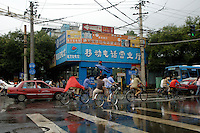 People riding bikes along a busy city street, Beijing, China.