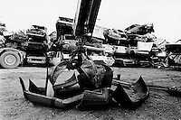 Italy. Veneto Region. Vicenza. Cars scrapyard. Bumpers are loaded  with a crane into a lorry. The polyprophylene bumpers are carried away by a special truck from the Himont company for future recycling. Pile of derelectic motor vehicles . © 1993 Didier Ruef .