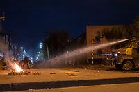 BOGOTA - COLOMBIA, 25-05-2021: Manifestantes se protegen del chorro de agua lanzado por una tanqueta del ESMAD (Escuadrón Móvil Antidisturbios de la Policía) durante los disturbios en el sector de las Américas de la ciudad de Bogotá durante el día 28 del Paro Nacional en Colombia hoy, 25 de mayo de 2021, para protestar contra el gobierno de Ivan Duque además de la precaria situación social y económica que vive Colombia. El paro fue convocado por sindicatos, organizaciones sociales, estudiantes y la oposición. / Protesters protect themselve from the jet of water launched by an ESMAD tank (Police Anti-Riot Mobile Squad) during the riots at Portal Las Americas sector of the city of Bogota during the day 28 of the National strike in Colombia today, May 25, 2021, to protest against the government of Ivan Duque in addition to the precarious social and economic situation that Colombia is experiencing. The strike was called by unions, social organizations, students and the opposition in Colombia. Photo: VizzorImage / Diego Cuevas / Cont