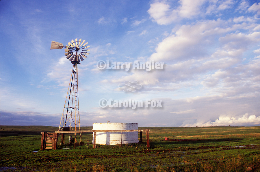 Aermotor windmill and water tank, clouds, California.