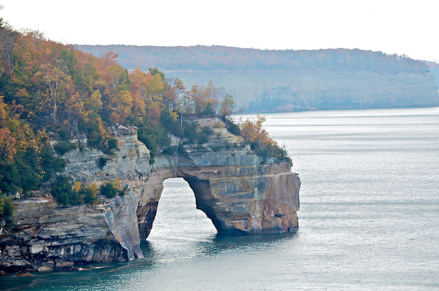 The fall colors at Pictured Rocks National Lakeshore. The arched rock formation is affectionately called Lovers Leap according to local folklore. Munising, MI
