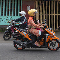 Yogyakarta, Java, Indonesia.  Road Safety.  Little Girl Sucking her Thumb while Riding with her Mother on a Motorbike.