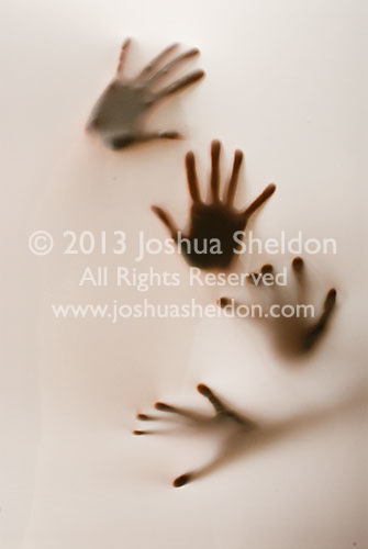 Two pair of hands partially silhouetted behind translucent fabric<br />