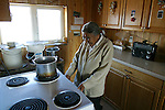 Vuntut Gwitchin First Nation elder Edith Josie puts a pot on her stove inside her home in Old Crow, Yukon Territory, Canada.