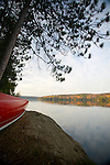 A red canoe by the water of Galerairy Lake in Ontario's Algonquin Provincial Park in Canada.