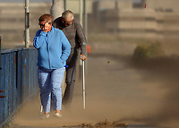 """Pictured: A couple struggle to walk against the strong wind and sand blasted from the beach on Oystermouth Road from the beach in Swansea, UK. Monday 16 October 2017<br /> Re: Remnants of Hurricane Ophelia are expected to bring strong gusts of wind to Wales when it hits Britain's shores.<br /> The hurricane, making its way from the Azores in the Atlantic Ocean, will have weakened to a storm when it arrives.<br /> A Met Office amber """"be prepared"""" warning has been issued in some areas bringing """"potential danger to life""""."""