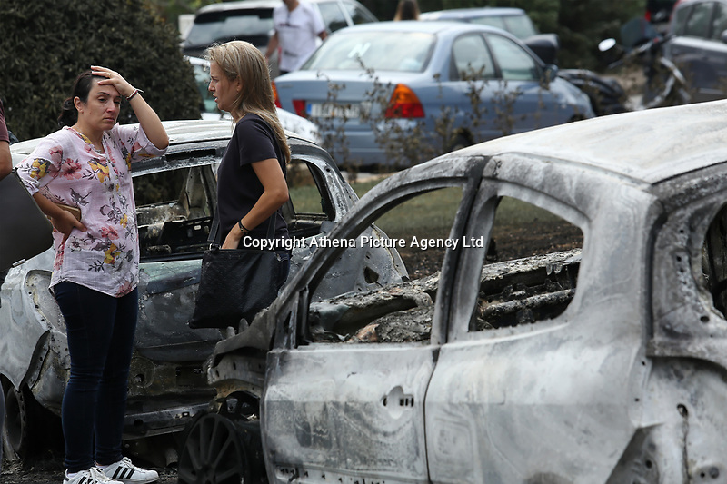 Pictured: Local people in the aftermath of the wild forest fires in the Mati area near Rafina, Greece. Tuesday 24 July 2018<br /> Re: Deaths caused by wild forest fires throughout Greece.