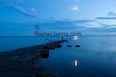Great Britain, England, Dorset, Kimmeridge: Stone pier and moon at Kimmeridge Bay | Grossbritannien, England, Dorset, Kimmeridge: Mann fotografiert Reflexion des Mondes im Wasser der Kimmeridge Bay