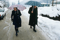 Bosnia and Herzegowina. Republika Serpska. Srebrenica. Two old serb women, wearing black clothes,  walk on the concrete road and protect themselves from the falling snow with an umbrella during the winter season.© 2005 Didier Ruef