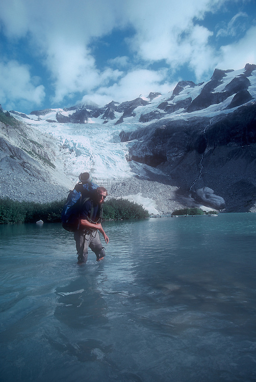 North Cascades National Park, National Outdoor Leadership School climber fording outflow of Moraine Lake, Cascade Mountains, Washington State, Pacific Northwest, U.S.A.,