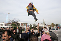 Pictured: A man throws his young child up in the air during the protest Monday 06 February 2017<br /> Re: Scuffles between migrants and police broke out during a visit by Immigration Policy Minister Yiannis Mouzalas at the Elliniko migrant camp located in the former airport in the outskirts of Athens, Greece.