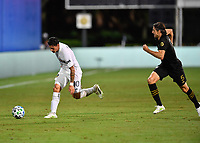 LAKE BUENA VISTA, FL - JULY 18: Cristian Pavón #10 of LA Galaxy dribbles away from Dejan Jakovic #5 of LAFC during a game between Los Angeles Galaxy and Los Angeles FC at ESPN Wide World of Sports on July 18, 2020 in Lake Buena Vista, Florida.