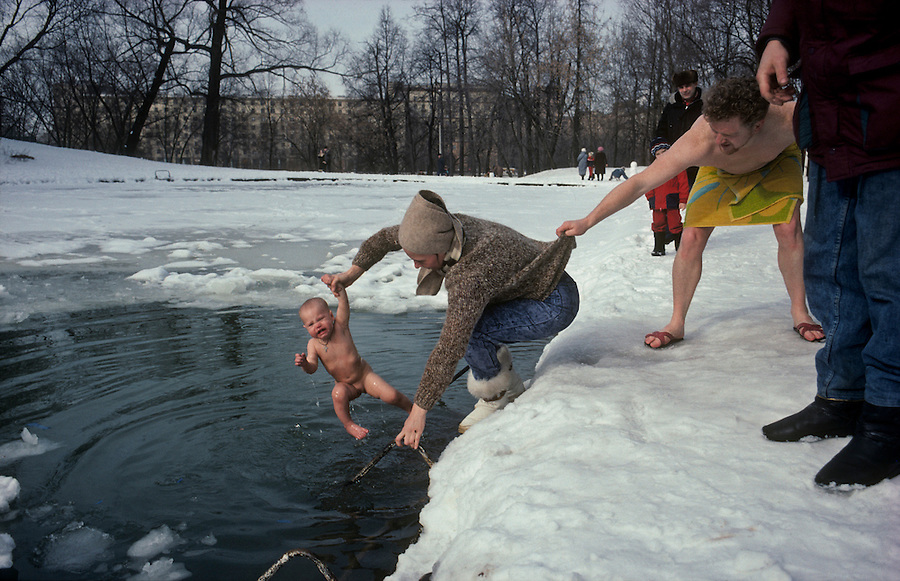 Gorky Park, Moscow, Russia..The Maxim Gorky Central Park of Culture and Rest was the first such park in the Soviet Union, and it remains the largest in Russia; some 10 million people visit each year. A group of ice swimmers, known as walruses, dip a baby girl in a park lake in temperatures of minus 18C.