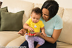 10 month old baby girl at home with mother shown bell toy, trying to make it ring herself after mother demonstrated it