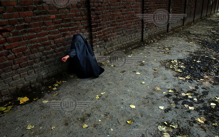 A women dressed in a burqa begs for money.