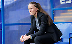 Manchester United manager Casey Stoney sits in the dugout before the start of the match