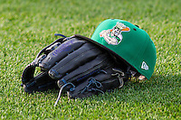 A Clinton LumberKings hat sits atop a glove in the outfield prior to a Midwest League game against the Wisconsin Timber Rattlers on May 9th, 2016 at Fox Cities Stadium in Appleton, Wisconsin.  Clinton defeated Wisconsin 6-3. (Brad Krause/Four Seam Images)
