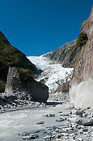 Waiho River running next to the valley wall. Franz Josef Glacier in the background - Westland National Park, West Coast