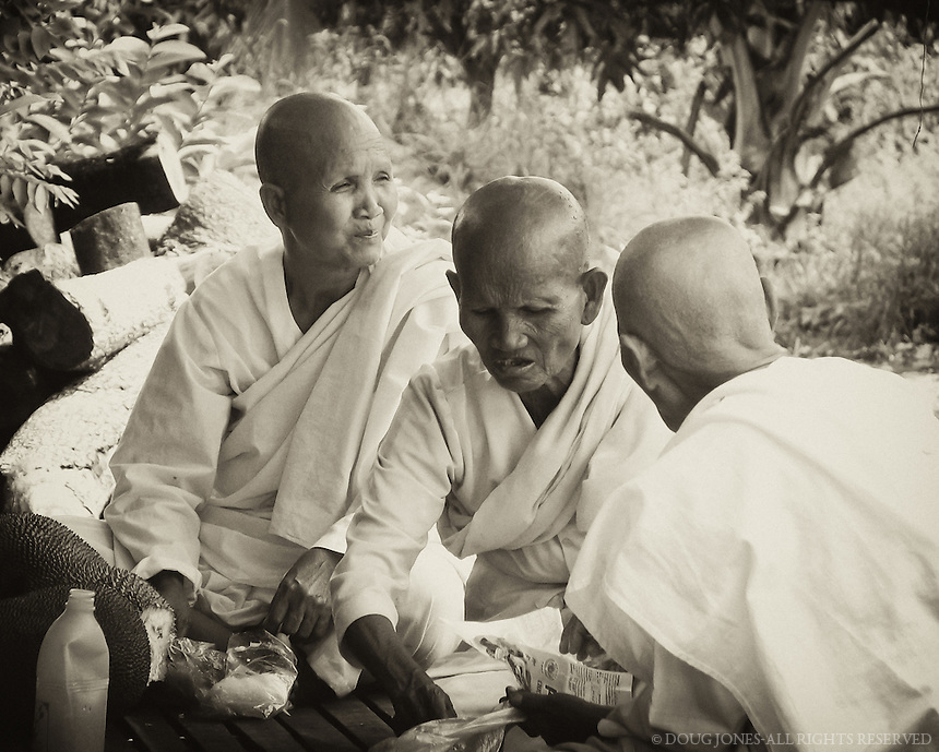 These Buddhist nuns were taking a break from their crowded van at a roadside market in southern Cambodia.  It was unbearably hot and humid, and I marveled at how stoic and refreshed these women appeared while relaxing under a shade tree.