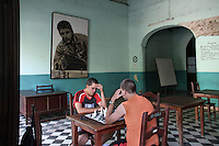 Two Cubans play chess in a club under the portrait of revolutionary Enrnesto Che Gueavara in dowtown Havana