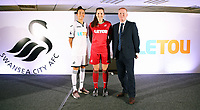 Pictured: Katy Hosford (RED) and Alicia Powe (WHITE) of the Swansea City FC Ladies' team model the home and away kits with Dsability Sport Wales representative. Monday 19 June 2017<br />