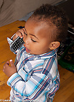 17 month old toddler boy holding cell telephone to ear and talking
