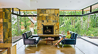 Invisible glass doors as windows, connecting living room with fireplace with outdoor garden.