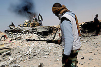 Rebel fighters stand among the wreckage of government tanks following an intense battle for the town of Ajdabiya. .On 17 February 2011, an uprising against the 41 year rule of Col Muammar Gadaffi started in eastern Libya..