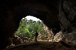 Tourist standing at the entrance to a large cave. Ankarana National Park, northern Madagascar